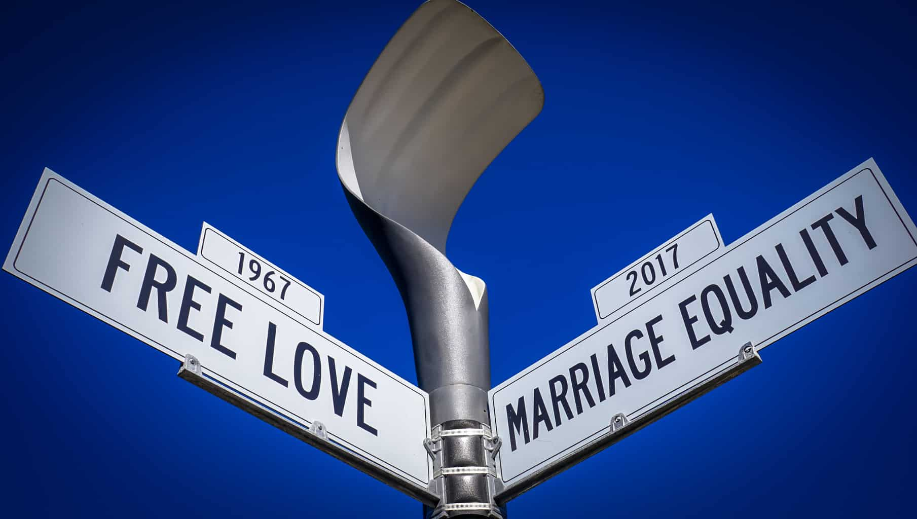 """Street signs with sky above, """"free love"""" and """"marriage equality"""""""