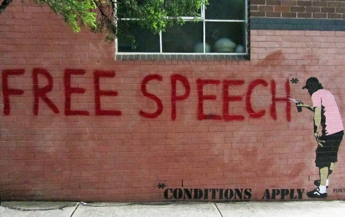 Image of red free speech in capitals on brick wall with graffiti artist spraying