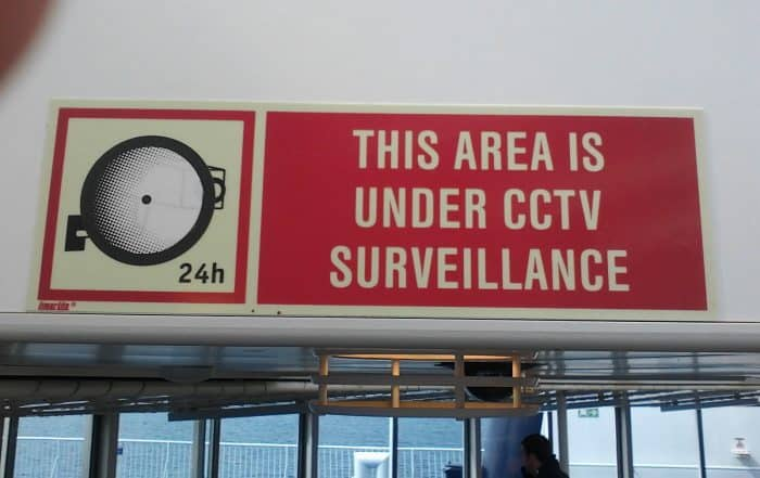 Red sign notifying of surveillance