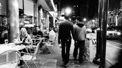 Two guys walking in the street at night