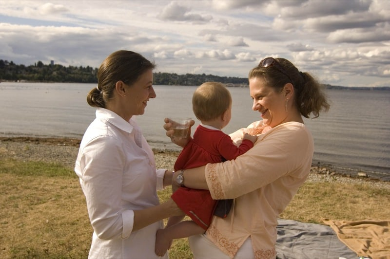 Two women with baby by river