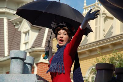 Image of Mary Poppins in red dress with purple scarf carrying black umbrella