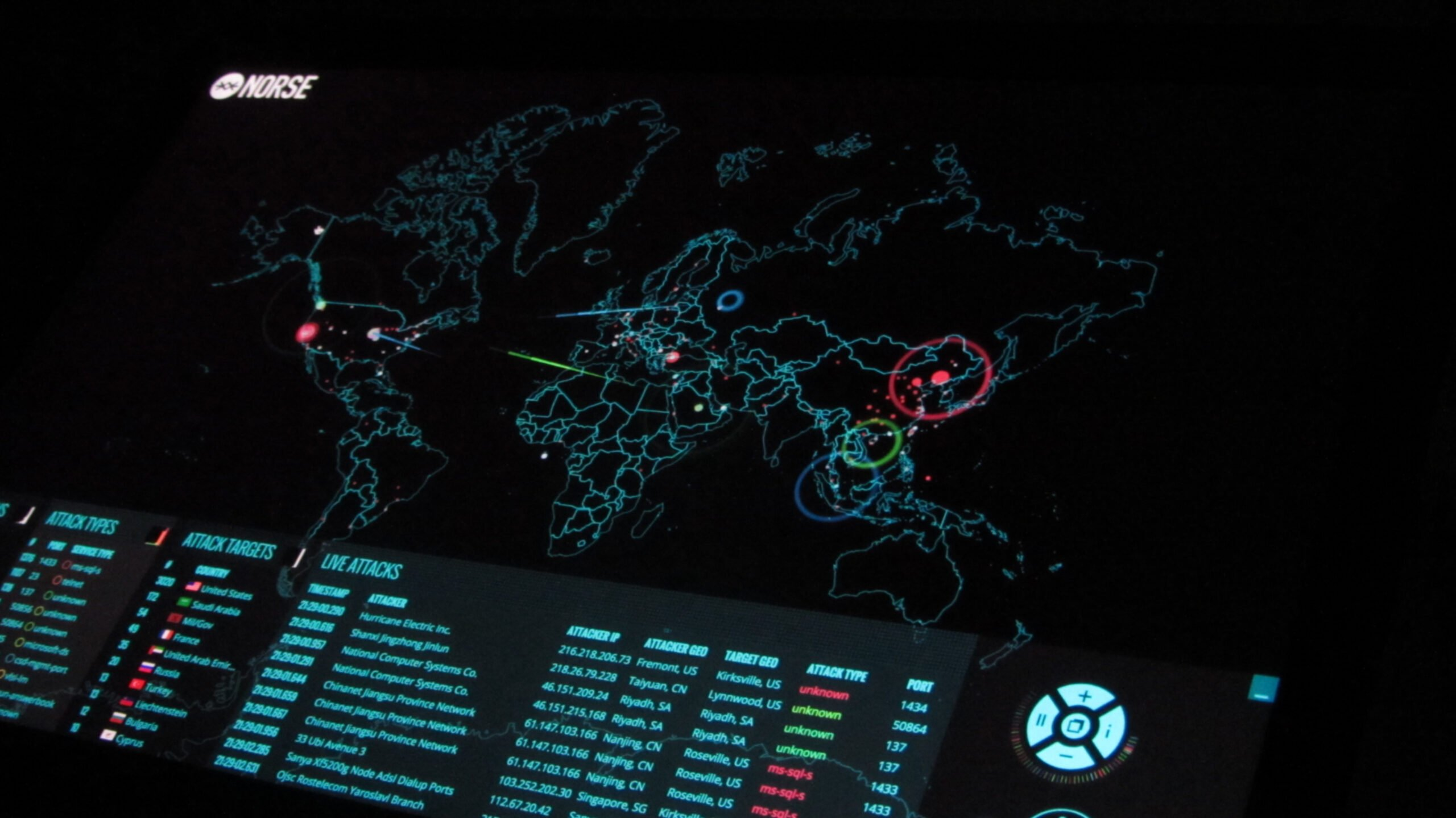 Computer dashboard in digital showing cyber attacks across the world with coloured lines on a map